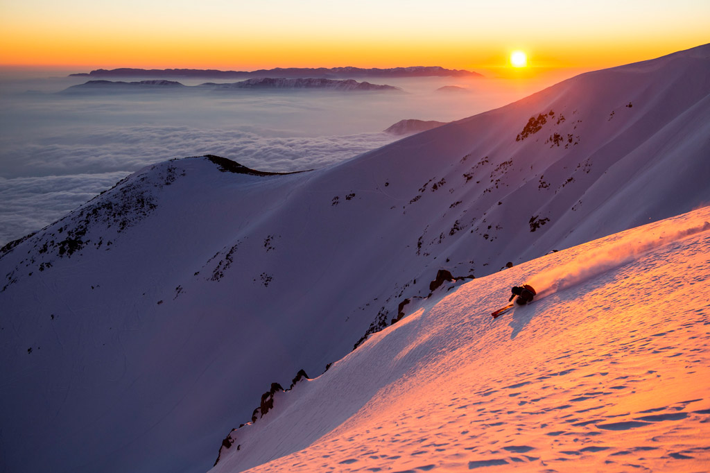 A skier skiing down at sunset at Ski Arpa Chile