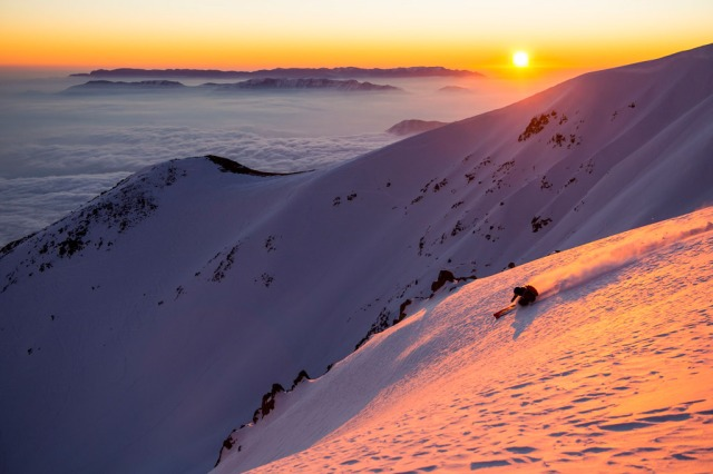 A skier skiing down at sunset at Ski Arpa Chile