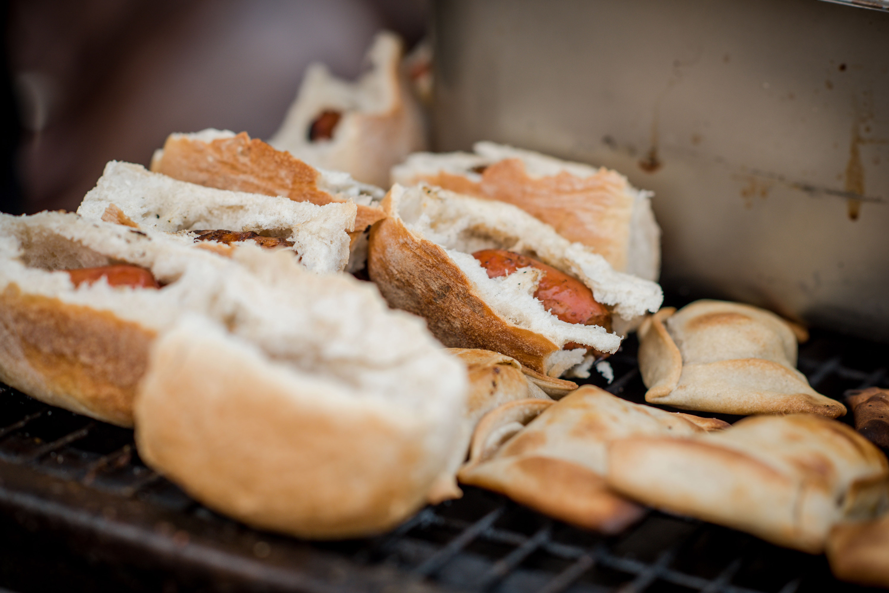 Choripan or bread and chorizo alongside some empanadas on the grill for a barbecue at the winery.